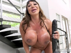 Busty lady in tiny outfit sits down on a long black sex toy