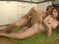A redhead is on the kitchen floor and besides she is getting fucked hard