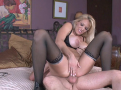 A blonde with big boobs removes her panties and then rides a knob