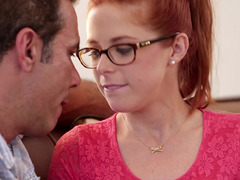 A redhead with glasses is getting pushed and moreover fucked against the sofa