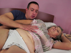 Overweight granny is licking a young phallus on the bed in this vid