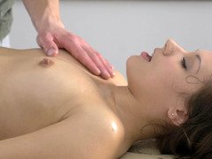 A chick that is smeared with oil on the massage table is sitting on a purple rod