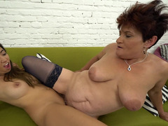 A brunette minx is with a redhead granny on the sofa, fucking