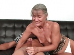 Aged granny tugging fuck tool on couch