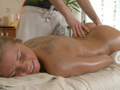 An oiled up redhead is getting taken on the massage table