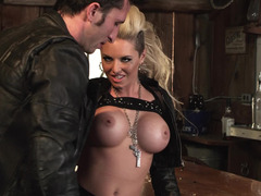 A bimbo with huge fake tits is in a bar and she is getting fucked