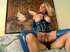 Bossy towheaded humped on a bed in latex gloves a corset and stockings