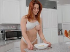 Busty redhead plays solo with vibrator on the kitchen table