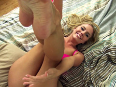 A blonde licks her black dong while she is on the bed alone