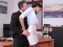 A gal is with her boss in the office and she is spreading her legs for him