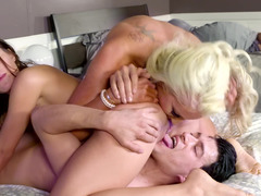 A blonde and a brunette are on the bed, getting fucked well