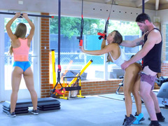 A pair of glamorous sportswomen perform threesome in the gym