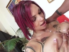 A sexy slut with tattoos and large tits is giving a blow job to a man