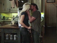 A blonde is getting undressed in the kitchen to have some sex