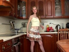 A blonde is in the kitchen, sitting down on a big rubber dildo