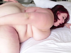 A fat redhead is riding a large cock of her skinny dude on the bed