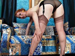 Ruttish redhead in sexy stockings takes off her clothes