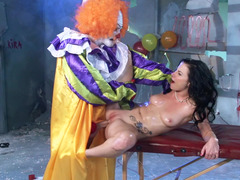 A cute thing is getting fucked by a clown on the massage table